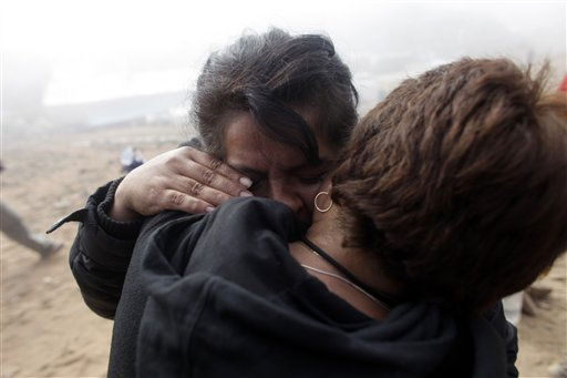 Relatives of trapped miners embrace at the San Jose Mine near  Copiapo, Chile,  Saturday, Oct. 9, 2010. Officials have announced that the drill trying to reach the 33 trapped miners has reached them after more than two months of efforts, prompting cheers, tears and the ringing of bells by families in the tent camp outside the mine.&#40;AP Photo&#47;Dario Lopez-Mills&#41; <span class=meta>(AP Photo&#47; Dario Lopez-Mills)</span>