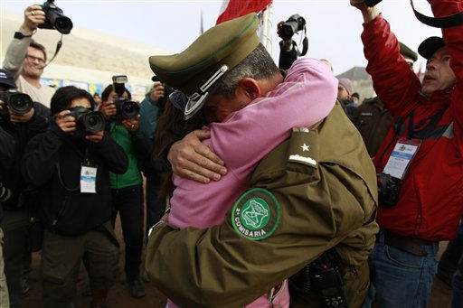 A chilean police officer embraces a relative of trapped miners  after it was announced that a drill reached the underground cave where miners are at the San Jose Mine near Copiapo, Chile Saturday, Oct. 9, 2010. Officials have announced that the drill trying to reach the 33 trapped miners has reached them after more than two months of efforts, prompting cheers, tears and the ringing of bells by families in the tent camp outside the mine.&#40;AP Photo&#47;Roberto Candia&#41; <span class=meta>(AP Photo&#47; Roberto Candia)</span>