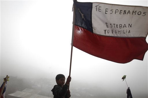 A boy waves a Chilean flag as he celebrates after it was announced that a drill reached the trapped miners at the San Jose Mine near Copiapo,  Chile,  Saturday, Oct. 9,  2010.  A drill reached the miners at a point 2,041 feet &#40;622 meters&#41; below the surface at 8:05 a.m., after 33 days of drilling. &#40;AP Photo&#47; Naracha Pisarenko&#41; <span class=meta>(AP Photo&#47; Natacha Pisarenko)</span>