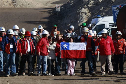 Relatives of trapped miners, one holding a Chilean flag,  accompanied by mining officials and people involved in the rescue efforts react  after it was announced that a drill reached the trapped miners at the San Jose Mine near  Copiapo,  Chile,  Saturday, Oct. 9,  2010.  Officials have announced that the drill trying to reach the 33 trapped miners has reached them after more than two months of efforts, prompting cheers, tears and the ringing of bells by families in the tent camp outside the mine.&#40;AP Photo&#47;Dario Lopez-Mills&#41; <span class=meta>(AP Photo&#47; Dario Lopez-Mills)</span>