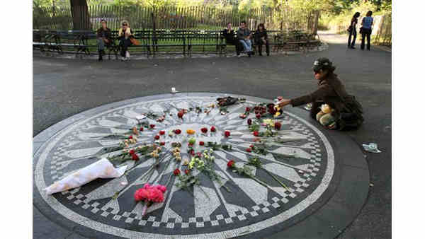 Julia Balk, seated right, spreads flower petals on the Imagine mosaic as she spends time in Strawberry Fields in New York&#39;s Central Park on Saturday, Oct. 9, 2010, the day that would have been John Lennon&#39;s 70th birthday. &#40;AP Photo&#47;Tina Fineberg&#41; <span class=meta>(AP Photo&#47; Tina Fineberg)</span>