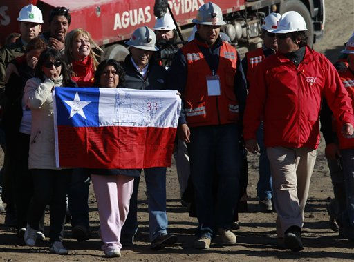 Relatives of trapped miners, one holding a Chilean flag,  accompanied by mining officials and people involved in the rescue efforts react after it was announced that a drill reached the trapped miners at the San Jose Mine near  Copiapo,  Chile,  Saturday, Oct. 9,  2010.  Officials have announced that the drill trying to reach the 33 trapped miners has reached them after more than two months of efforts, prompting cheers, tears and the ringing of bells by families in the tent camp outside the mine. &#40;AP Photo&#47;Dario Lopez-Mills&#41; <span class=meta>(AP Photo&#47; Dario Lopez-Mills)</span>