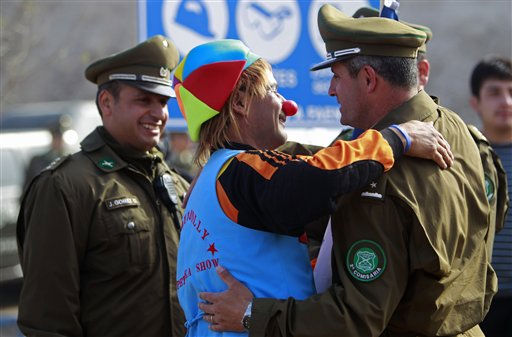 Rolando Gonzalez, center, a miner who doubles as a clown to entertain children at the camp where relatives of trapped miners wait for the rescue, celebrates with police officers at the San Jose mine near Copiapo, Chile, Saturday, Oct. 9, 2010. Officials announced that the drill trying to reach the 33 trapped miners reached them after more than two months of efforts, prompting cheers, tears and the ringing of bells by families in the tent camp outside the mine. &#40;AP Photo&#47;Natacha Pisarenko&#41; <span class=meta>(AP Photo&#47; Natacha Pisarenko)</span>
