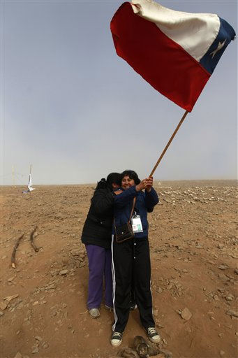 Relatives of trapped miners embrace as they wave a Chilean flag at the San Jose mine near Copiapo, Chile Saturday, Oct. 9, 2010. A drilling rig punched through to the underground site where the 33 miners have been trapped for 66 days under the Chilean desert, raising cheers, tears and hopes. &#40;AP Photo&#47;Roberto Candia&#41; <span class=meta>(AP Photo&#47; Roberto Candia)</span>