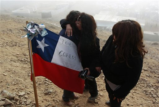 Relatives of trapped miners embrace next to a Chilean flag at the San Jose mine near Copiapo, Chile Saturday, Oct. 9, 2010. A drilling rig punched through to the underground site where the 33 miners have been trapped for 66 days under the Chilean desert, raising cheers, tears and hopes. &#40;AP Photo&#47;Roberto Candia&#41; <span class=meta>(AP Photo&#47; Roberto Candia)</span>
