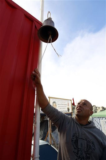 "<div class=""meta ""><span class=""caption-text "">A man sounds a bell as news in celebration at the San Jose Mine near Copiapo, Chile Saturday, Oct. 9, 2010. A drilling rig punched through to the underground site where the 33 miners have been trapped for 66 days under the Chilean desert, raising cheers, tears and hopes. (AP Photo/Roberto Candia) (AP Photo/ Roberto Candia)</span></div>"