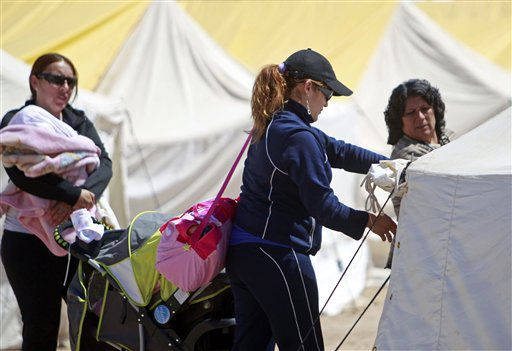Elizabeth Segovia, center, opens her tent as she arrives with her daughter, Esperanza Ticona, not seen inside the baby stroller, at the camp where relatives wait for the rescue of trapped miners outside the San Jose mine near Copiapo, Chile, Saturday, Oct. 9, 2010. A drilling rig punched through to the underground site where the 33 miners have been trapped for 66 days under the Chilean desert, raising cheers, tears and hopes. Esperanza was born while his father was trapped at the mine. &#40;AP Photo&#47;Natacha Pisarenko&#41; <span class=meta>(AP Photo&#47; Natacha Pisarenko)</span>