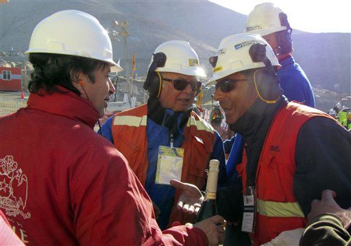 "<div class=""meta ""><span class=""caption-text "">Chile's Minister of Mining Laurence Golborne, left, holds up a bottle of champagne as he speaks to unidentified members of the rescue team after the T-130 drill reached the 33 trapped miners at the San Jose mine near Copiapo, Chile Saturday Oct. 9, 2010. A drilling rig punched through to the underground site where the 33 miners have been trapped for 66 days under the Chilean desert, raising cheers, tears and hopes. (AP Photo) (AP Photo/ Anonymous)</span></div>"