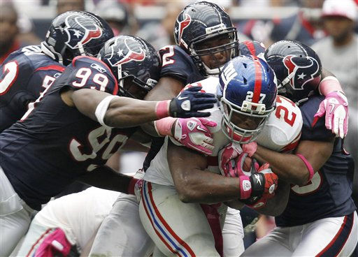 New York Giants&#39; Brandon Jacobs &#40;27&#41; pulls along four Houston Texans defenders, including Adewale Ogunleye &#40;99&#41;, in the fourth quarter of an NFL football game Sunday, Oct. 10, 2010, in Houston. The Giants won 34-10. &#40;AP Photo&#47;Eric Gay&#41; <span class=meta>(AP Photo&#47; Eric Gay)</span>