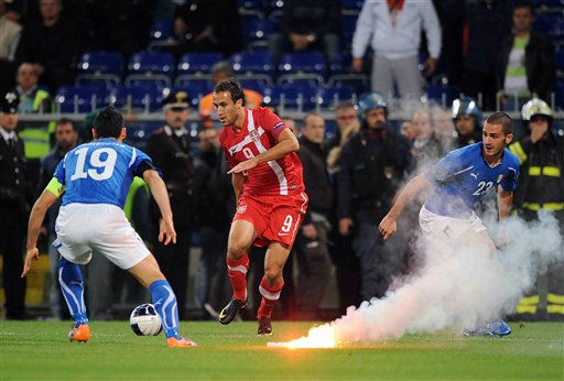 Italy&#39;s Gianluca Zambrotta, left, vies for the ball with Serbia&#39;s Dragan Mrdja and Italy&#39;s Leonardo Bonucci, right next to a burning flare thrown onto the pitch by Serbia supporters, not pictured, during the Group C, Euro 2012 qualifying soccer match between Italy and Serbia is suspended, at the Luigi Ferraris stadium in Genoa, Italy, Tuesday, Oct. 12, 2010. The Italy-Serbia European Championship qualifier was called off after seven minutes of play on Tuesday after Serbia fans threw flares and fireworks onto the pitch. &#40;AP Photo&#47;Fabio Ferrari, Lapresse&#41; ** ITALY OUT ** <span class=meta>(AP Photo&#47; Fabio Ferrari)</span>