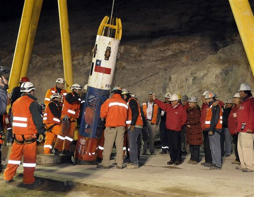 In this photo released by the Chilean presidential press office, Chile&#39;s President Sebastian Pinera, center right in red jacket, waves to rescue worker Manuel Gonzalez Paves as he is lowered into the mine in the capsule to begin the rescue of 33 trapped miners at the San Jose Mine near Copiapo, Chile, Tuesday Oct. 12, 2010. The first of 33 trapped miners is expected to be lifted to the surface late Tuesday after surviving more than two months below ground. &#40;AP Photo&#47;Alex Ibanez, Chilean presidential press office&#41; <span class=meta>(AP Photo&#47; Alex Ibanez)</span>