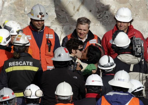 Miner Alex Vega Salazar, center left, kisses his wife Jessica Salgado after emerging from the capsule that brought him to the surface from the collapsed San Jose gold and copper mine near Copiapo, Chile, Wednesday, Oct. 13, 2010. Vega is the tenth of 33 miners who was rescued from the mine after more than 2 months trapped underground. &#40;AP Photo&#47;Jorge Saenz&#41; <span class=meta>(AP Photo&#47; Jorge Saenz)</span>