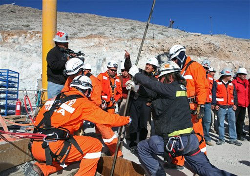 In this photo released by the Chilean government, Bolivian President Evo Morales, center right at rear, gestures as rescuers operate the capsule that is bringing the trapped miners to the surface from the collapsed San Jose gold and copper mine near Copiapo, Chile, Wednesday, Oct. 13, 2010.  &#40;AP Photo&#47;Hugo Infante, Chilean government&#41; <span class=meta>(AP Photo&#47; Hugo Infante)</span>