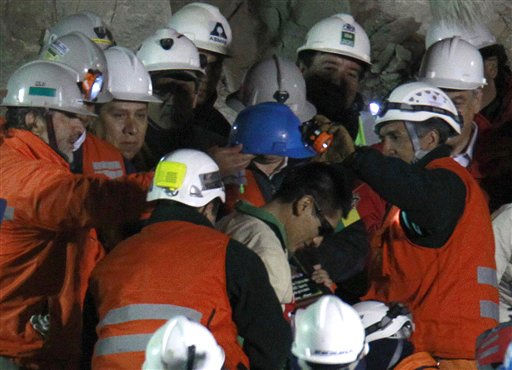 Rescue workers put a helmet back on rescued miner Carlos Mamani Solis, of Bolivia, after it fell off after he was rescued from the collapsed San Jose gold and copper mine where he was trapped with 32 other miners for over two months near Copiapo, Chile, Wednesday Oct. 13, 2010.  &#40;AP Photo&#47;Roberto Candia&#41; <span class=meta>(AP Photo&#47; Roberto Candia)</span>