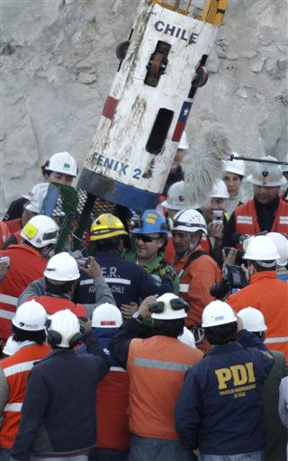 Miner Franklin Lobos, center wearing blue had, exits the capsule that lifted him to the surface after being rescued from the collapsed San Jose gold and copper mine where he had been trapped with 32 other miners for over two months near Copiapo, Chile, Wednesday Oct. 13, 2010.   &#40;AP Photo&#47;Jorge Saenz&#41; <span class=meta>(AP Photo&#47; Jorge Saenz)</span>