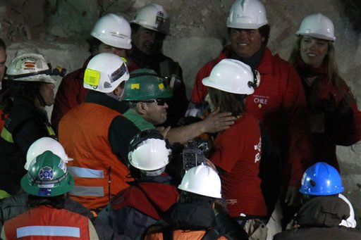 Rescued miner Jose Ojeda, center left wearing green helmet, reaches out to hug a relative after emerging from the capsule that brought him to the surface from the collapsed San Jose gold and copper mine where he was trapped with 32 other miners for over two months near Copiapo, Chile, early Wednesday Oct. 13, 2010. &#40;AP Photo&#47;Roberto Candia&#41; <span class=meta>(AP Photo&#47; Roberto Candia)</span>