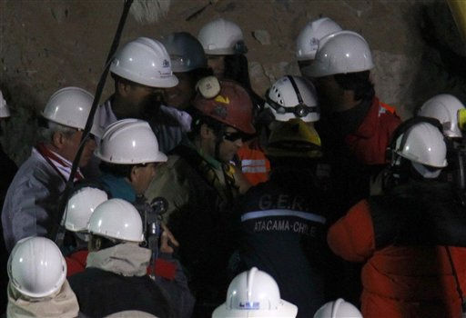 Rescued miner Florencio Antonio Avalos Silva center is seen among rescue workers after coming out of the capsule after he was rescued from the collapsed San Jose gold and copper mine where he was trapped with 32 other miners for over two months near Copiapo, Chile,  early Wednesday, Oct. 13, 2010.&#40;AP Photo&#47;Roberto Candia&#41; <span class=meta>(AP Photo&#47; Roberto Candia)</span>