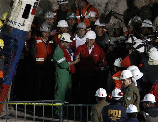 Miner Luis Urzua, the last miner to be rescued, left wearing green, shakes hands with Chile&#39;s President Sebastian Pinera after being rescued from the collapsed San Jose gold and copper mine where he had been trapped with 32 other miners for over two months near Copiapo, Chile, Wednesday Oct. 13, 2010. The 69-day underground ordeal reached its end Wednesday night after 33 trapped miners were hauled up in a cage through a narrow hole drilled through 2,000 feet of rock.  &#40;AP Photo&#47;Roberto Candia&#41; <span class=meta>(AP Photo&#47; Roberto Candia)</span>