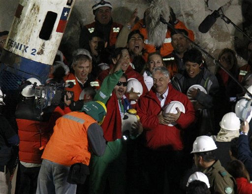 Miner Luis Urzua, the last miner to be rescued, center wearing green, celebrates next to Chile&#39;s President Sebastian Pinera after being rescued from the collapsed San Jose gold and copper mine where he had been trapped with 32 other miners for over two months near Copiapo, Chile, Wednesday Oct. 13, 2010. The 69-day underground ordeal reached its end Wednesday night after 33 trapped miners were hauled up in a cage through a narrow hole drilled through 2,000 feet of rock. &#40;AP Photo&#47;Roberto Candia&#41; <span class=meta>(AP Photo&#47; Roberto Candia)</span>