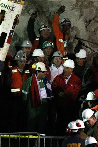 "<div class=""meta ""><span class=""caption-text "">The last rescued miner Luis Urzua, center left wearing green, talks to Chile's President Sebastian Pinera after being rescued from the collapsed San Jose gold and copper mine where he had been trapped with 32 other miners for over two months near Copiapo, Chile, Wednesday Oct. 13, 2010. The 69-day underground ordeal reached its end Wednesday night after 33 trapped miners were hauled up in a cage through a narrow hole drilled through 2,000 feet of rock. (AP Photo/Roberto Candia) (AP Photo/ Roberto Candia)</span></div>"