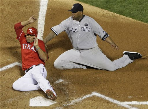 New York Yankees starting pitcher CC Sabathia, right, tags out Texas Rangers&#39; Nelson Cruz attempting to score on a wild pitch in the first inning of Game 1 of baseball&#39;s American League Championship Series Friday, Oct. 15, 2010, in Arlington, Texas. &#40;AP Photo&#47;Paul Sancya&#41; <span class=meta>(AP Photo&#47; Paul Sancya)</span>