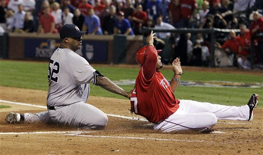 New York Yankees starting pitcher CC Sabathia, left, tags out Texas Rangers&#39; Nelson Cruz attempting to score on a wild pitch in the first inning of Game 1 of baseball&#39;s American League Championship Series Friday, Oct. 15, 2010, in Arlington, Texas. &#40;AP Photo&#47;Tony Gutierrez&#41; <span class=meta>(AP Photo&#47; Tony Gutierrez)</span>