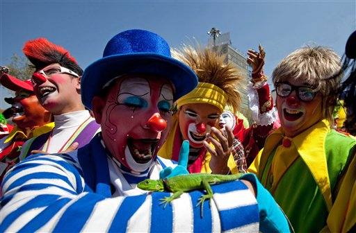 A clown plays with a lizard as others laugh while trying to break the &#34;laugh world record&#34; in Mexico City, Wednesday, Oct. 20, 2010. Hundreds of clowns are attending the XVth International Clown Convention in the Mexican capital.  <span class=meta>(&#40;AP Photo&#47;Claudio Cruz&#41;)</span>