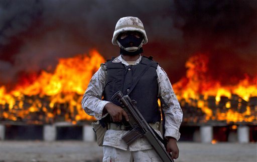 "<div class=""meta image-caption""><div class=""origin-logo origin-image ""><span></span></div><span class=""caption-text"">A soldier guards next to packages of marijuana that are being incinerated in Tijuana, Mexico, Wednesday, Oct. 20, 2010. On a conjoined operation with the army, local and state police seized 134 tons of U.S.-bound marijuana Monday, by far the biggest drug bust in the country in recent years. Eleven suspects were detained. ((AP Photo/Guillermo Arias))</span></div>"