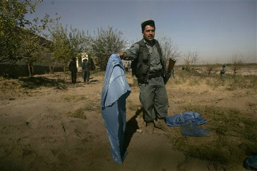 An Afghan policeman holds up a burqa worn by one of the people that attacked a UN compound in Herat, west of Kabul, Afghanistan, Saturday, Oct. 23, 2010. A suicide car bomber and three armed militants wearing explosives vests and burqas attacked the compound Saturday, but Afghan security forces killed the attackers and no U.N. employees were harmed, officials said. &#40;AP Photo&#47;Reza Shirmohammadi&#41; <span class=meta>(AP Photo&#47; Reza Shirmohammadi)</span>
