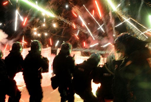 "<div class=""meta ""><span class=""caption-text "">Police officers take cover as demonstrators aim fireworks at them in Terzigno, near Naples, during clashes in the early hours of Saturday, Oct. 23, 2010. People demonstrating against plans to build a garbage dump near Naples hurled stones and firecrackers at police and set vehicles ablaze, as the confrontation continued during most of the night. The residents were protesting the stench and poor conditions of the local dump, as well as plans to open a new one in the Vesuvio National Park. (AP Photo/Salvatore Laporta) (AP Photo/ Salvatore Laporta)</span></div>"