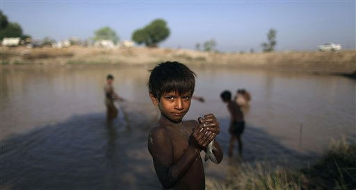 In this Monday, Nov. 1, 2010 picture, Shwun Ali, a boy whose family was displaced by floods, looks on while holding a fish he caught while fishing along with other boys in a flooded field next to their camp in Muzaffargarh in Punjab province, Pakistan. The floods that hit Pakistan in the summer of 2010 took 2,000 lives and affected 20 million people, of whom 7 million remain homeless. &#40;AP Photo&#47;Muhammed Muheisen&#41; <span class=meta>(AP Photo&#47; Muhammed Muheisen)</span>