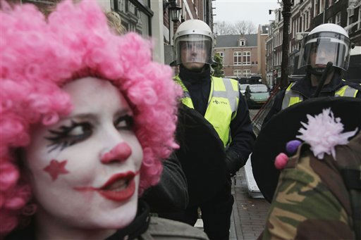 A demonstrator looks up as Dutch riot police, rear, close off a street in Amsterdam, Netherlands, Tuesday Nov. 9, 2010, as they proceed with clearing people squatting in unoccupied buildings. Dutch courts have ordered Amsterdam to suspend plans to evict squatters from empty buildings, ruling that a new law banning squatting is in conflict with European human rights treaties. Police were set to carry out the first evictions Tuesday under the ban that took effect Oct. 1. But Monday&#39;s rulings by appeals courts in Amsterdam and The Hague call into question whether the law can be enforced. A judge had ordered the specific building could be cleared. &#40;AP Photo&#47;Peter Dejong&#41; <span class=meta>(AP Photo&#47; Peter Dejong)</span>
