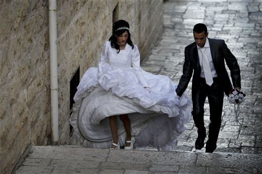 Israeli Moti Davido helps his bride-to-be Hodaya Leviyof with her dress as they pose for pictures before their wedding, in Jerusalem, Tuesday, Nov. 9, 2010.  Some Jews traditionally marry on Tuesday as in the Old Testament&#39;s text concerning the biblical creation, Tuesday is referred to twice in the phrase &#34;and God saw that it was good&#34; on that day. &#40;AP Photo&#47;Tara Todras-Whitehill&#41; <span class=meta>(AP Photo&#47; Tara Todras-Whitehill)</span>