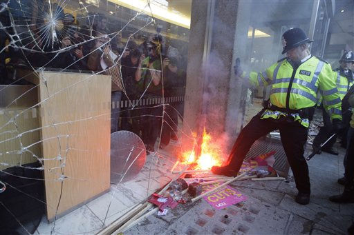 A British police officer tries to put out a fire as some thousands of students gather at the Conservative Party headquarter building in London, Wednesday, Nov. 10, 2010, to protest against plans to increase their student tuition fees and cut university funding. &#40;AP Photo&#47;Sang Tan&#41; <span class=meta>(AP Photo&#47; Sang Tan)</span>