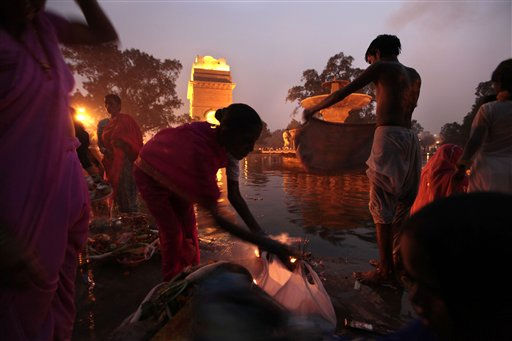 People gather their belongings after offering prayers and worshipping the Sun God at sunset during Chhath Puja festival in New Delhi, India, Friday, Nov. 12, 2010. On Chhath, an ancient Hindu festival, rituals are performed to thank the Sun God for sustaining life on earth. &#40;AP Photo&#47;Saurabh Das&#41; <span class=meta>(AP Photo&#47; Saurabh Das)</span>