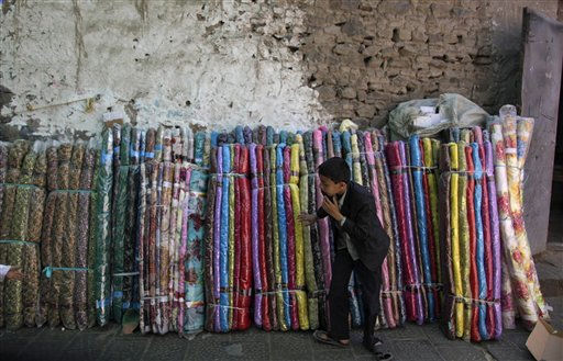 "<div class=""meta ""><span class=""caption-text "">A Yemeni boy selling bed sheets picks one for a customer in an alley of the old city of Sanaa, Yemen, Saturday, Nov. 13, 2010. (AP Photo/Muhammed Muheisen) (AP Photo/ Muhammed Muheisen)</span></div>"