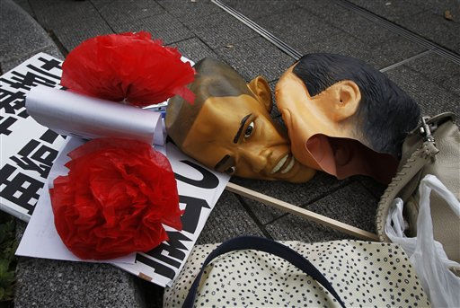 "<div class=""meta ""><span class=""caption-text "">Masks of U.S. President Barack Obama and Japanese Prime Minister Naoto Kan, right, lie on the ground during an anti-APEC demonstration near the APEC summit venue in Yokohama,  Japan, Saturday, Nov. 13,  2010.  AP Photo/Greg Baker) (AP Photo/ Greg Baker)</span></div>"