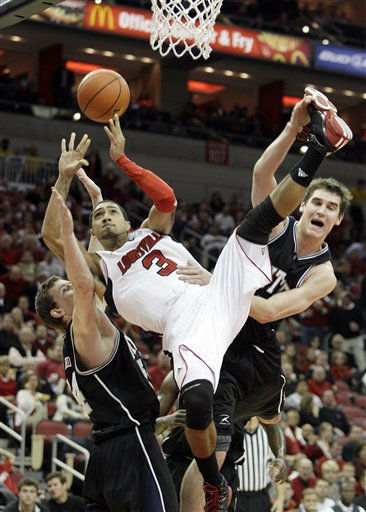Louisville guard Peyton Siva &#40;3&#41; shoots the ball as he falls between Butler players Matt Howard, left, and Andrew Smith during the second half of their NCAA college basketball game in Louisville, Ky., Tuesday, Nov. 16, 2010.  &#40;AP Photo&#47;Ed Reinke&#41; <span class=meta>(AP Photo&#47; Ed Reinke)</span>