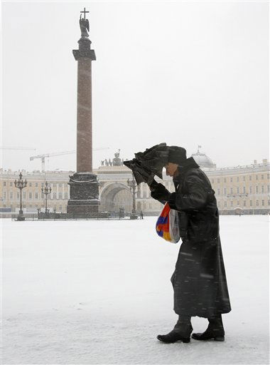 A Russian woman walks under snowfall at Dvortsovaya  Square in St.Petersburg, Russia, Thursday, Nov. 18, 2010. Low temperatures caused the first snowfalls in St.Petersburg. &#40;AP Photo&#47;Dmitry Lovetsky&#41; <span class=meta>(AP Photo&#47; Dmitry Lovetsky)</span>