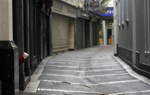 A man takes shelter in a doorway, left, as he begs for money on a deserted street in central Dublin, Ireland, Friday, Nov. 19, 2010. The euro is continuing to rise modestly against the dollar amid hopes of a resolution to Ireland&#39;s debt crisis. Ireland appears headed toward taking a loan from the European Union to bolster its debt-crippled banks, helping take the edge off recent fears about the resurgence of Europe&#39;s debt troubles.  &#40;AP Photo&#47;Peter Morrison&#41; <span class=meta>(AP Photo&#47; Peter Morrison)</span>