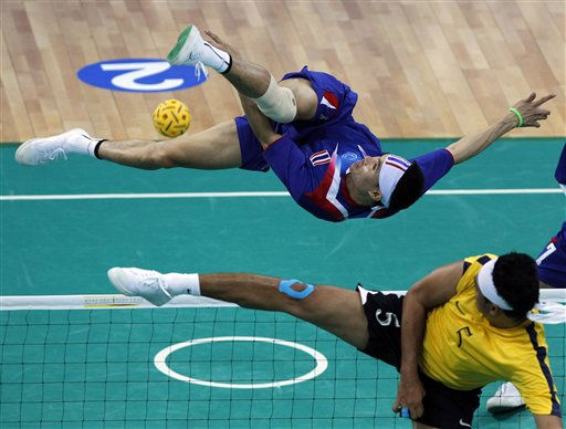 Thailand&#39;s Anuwat Chaichana, top, is airborne as he kicks the ball past Malaysia&#39;s Mohd Futra Abd Ghani during their men&#39;s team sepak takraw final match at the 16th Asian Games in Guangzhou, China, Saturday, Nov. 20, 2010. Thailand won the match 2-0 to clinch the gold medal. &#40;AP Photo&#47;Dita Alangkara&#41; <span class=meta>(AP Photo&#47; Dita Alangkara)</span>