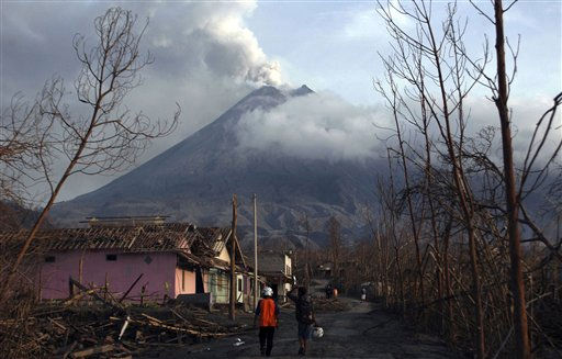 Villagers walk through destroyed houses in a village after the eruption of Mount Merapi at Umbulharjo in Cangkringan, Indonesia, Sunday, Nov. 21, 2010. Thousands of villagers have returned to their homes on the slopes of Indonesia&#39;s deadly volcano as it has become less active in recent days. &#40;AP Photo&#47;Slamet Riyadi&#41; <span class=meta>(AP Photo&#47; Slamet Riyadi)</span>
