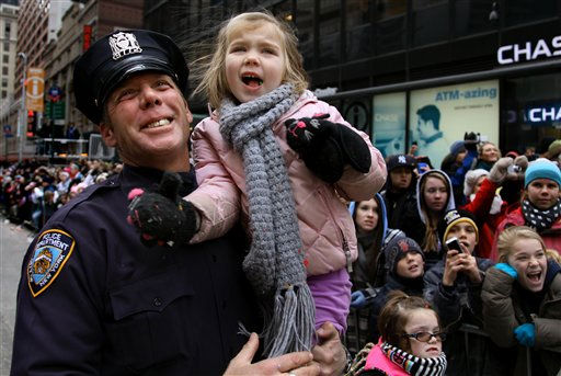 New York City police officer Wally Melvin holds his 5-year-old daughter Carlee as they watch Santa Claus pass by during the Macy's Thanksgiving Day Parade in New York Thursday, Nov. 25, 2010. (AP Photo/Craig Ruttle)