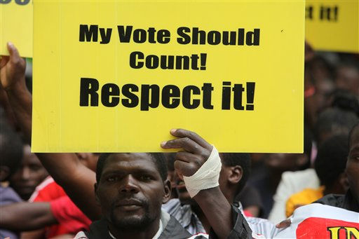 "<div class=""meta ""><span class=""caption-text "">A member of the Zimbabwe Human Rights Chapter holds a poster while waiting to be addressed  on the streets of Harare, Friday, December, 10, 2010. Thousands of people took to the streets of Harare, holding placards and marching in commemoration of World Human Rights Day.(AP Photo/Tsvangirayi Mukwazhi) (AP Photo/ Tsvangirayi Mukwazhi)</span></div>"