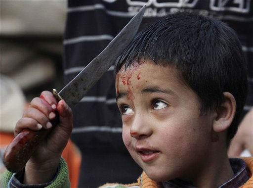 A Kashmiri Shiite Muslim boy bleeds as he flagellates himself during a Muharram procession in Srinagar, India, Tuesday, Dec. 14, 2010. Muharram is a month of mourning in remembrance of the martyrdom of Imam Hussein, the grandson of Prophet Mohammed. &#40;AP Photo&#47;Mukhtar Khan&#41; <span class=meta>(AP Photo&#47; Mukhtar Khan)</span>