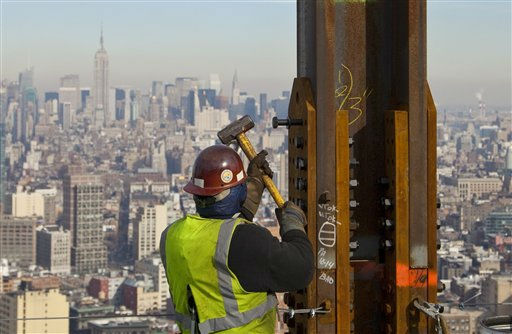 FILE- In this Dec. 16, 2010, file photo, an ironworker connects a steel plate to a column at One World Trade Center in New York. The Empire State Building is visible in the rear upper left. One World Trade Center, the giant monolith being built to replace the twin towers destroyed in the Sept. 11 attacks, will lay claim to the title of New York City?s tallest skyscraper on Monday, April 30, 2012, as workers erect steel columns that will make its unfinished skeleton a little over 1,250 feet, just high enough to peak over the observation deck on the Empire State Building. The milestone is a preliminary one. The so-called ?Freedom Tower? isn?t expected to reach its full height for at least another year, at which point it is likely to be declared the tallest building in the U.S.  &#40;AP Photo&#47;Mark Lennihan, File&#41; <span class=meta>(AP Photo&#47; Mark Lennihan)</span>