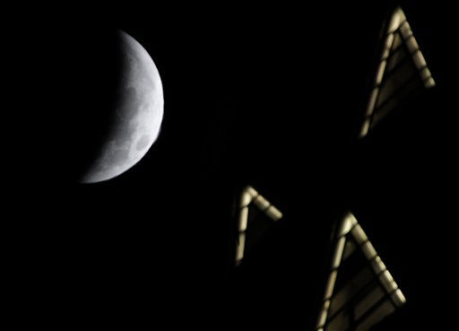 The moon, on its way to being totally eclipsed, is seen with the Chrysler Building in the foreground in New York, Tuesday, Dec. 21, 2010.  A total lunar eclipse occurs when the Earth casts its shadow on the full moon, blocking the sun&#39;s rays that otherwise reflect off the moon&#39;s surface. Some indirect sunlight still pierces through to give the moon its eerie hue. &#40;AP Photo&#47;Seth Wenig&#41; <span class=meta>(AP Photo&#47; Seth Wenig)</span>