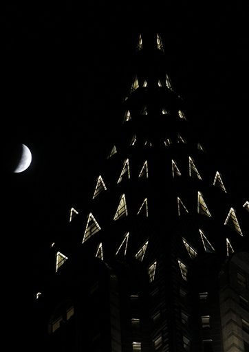 The moon on its way to being totally eclipsed is seen with the Chrysler Building in the foreground in New York, Tuesday, Dec. 21, 2010.  A total lunar eclipse occurs when the Earth casts its shadow on the full moon, blocking the sun&#39;s rays that otherwise reflect off the moon&#39;s surface.  &#40;AP Photo&#47;Seth Wenig&#41; <span class=meta>(AP Photo&#47; Seth Wenig)</span>