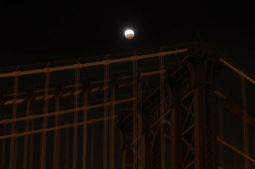 A partially eclipsed moon is seen over the Manhattan Bridge in New York, Tuesday, Dec. 21, 2010. A total lunar eclipse occurs when the Earth casts its shadow on the full moon, blocking the sun&#39;s rays that otherwise reflect off the moon&#39;s surface. Some indirect sunlight still pierces through to give the moon its eerie hue.  &#40;AP Photo&#47;Seth Wenig&#41; <span class=meta>(AP Photo&#47; Seth Wenig)</span>