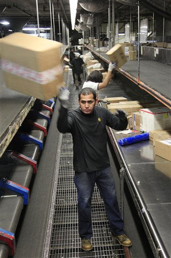 A UPS employee flips a box onto a conveyor belt at a UPS sorting facility, Wednesday, Dec. 22, 2010 in New York. Wednesday is the busiest day of the year for the Atlanta-based company. &#40;AP Photo&#47;Mark Lennihan&#41; <span class=meta>(AP Photo&#47; Mark Lennihan)</span>